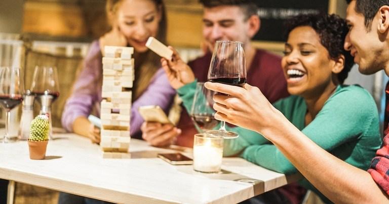 Un grupo de jóvenes adultos bebiendo vino y divirtiéndose con unos juegos durante sus vacaciones.