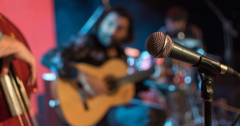 Una banda tocando música de los 80 en un escenario, con un micrófono en primer plano.