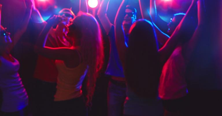 Un grupo de jóvenes bailando en una discoteca en los 80.
