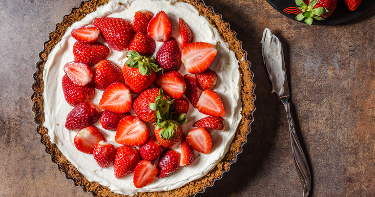 Una tarta de queso con fresas sobre una mesa con un cuchillo